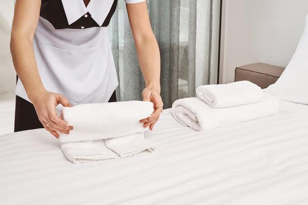 Bijgesneden portret van rollende handdoeken voor het schoonmaken van het huis op bed terwijl de slaapkamer wordt schoongemaakt en alles wordt voorbereid voor klanten om in te trekken, waardoor de kamer er netjes en opgeruimd uitziet. dienstmeisje deed haar best Gratis Foto