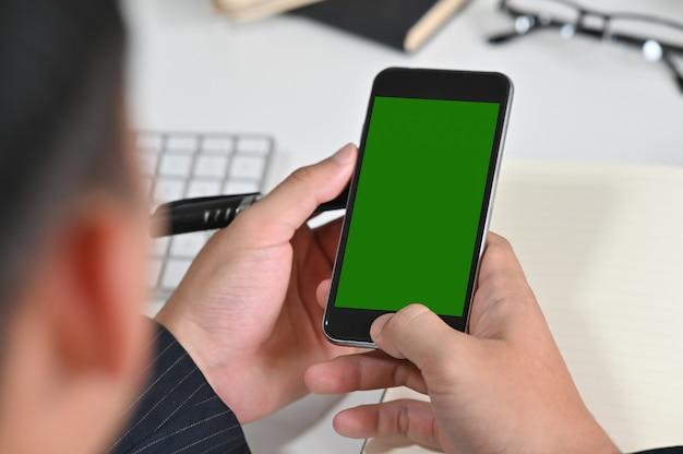 Bijgesneden schot man met mockup mobiele telefoon met groen scherm montage. Premium Foto
