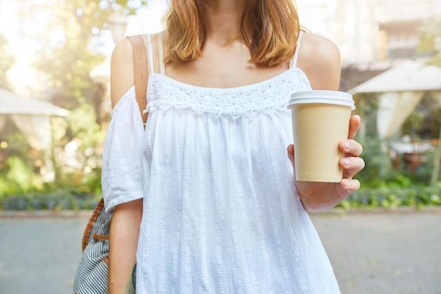 Bijgesneden schot van aantrekkelijke slanke jonge vrouw draagt witte zomerjurk met kopje afhaalmaaltijden koffie buiten wandelen in het park Gratis Foto