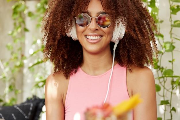 Bijgesneden schot van blije donkere vrouw met borstelige afro kapsel luistert favoriete afspeellijst in hoofdtelefoons, in goed humeur, modieuze zonnebril en roze t-shirt draagt, heeft stralende glimlach Gratis Foto