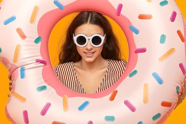 Bijgesneden schot van glamoureuze aantrekkelijke jonge vrouw die in ronde tinten roze opblaasbaar waterspeelgoed houdt Gratis Foto