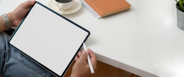 Bijgesneden schot van mannelijke freelancer werken met digitale tablet met notebook en koffiekopje Premium Foto