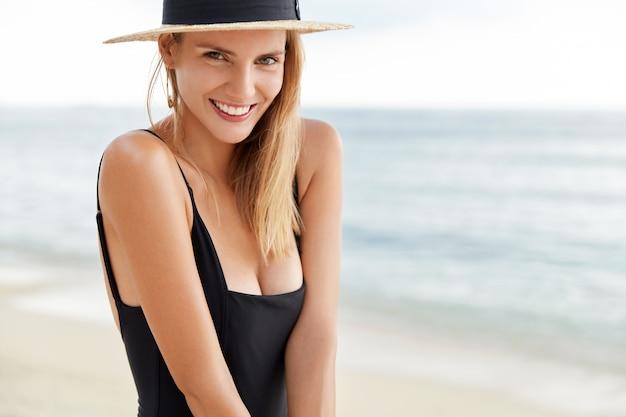 Bijgesneden schot van positieve mooie jonge vrouw recreëren op exotisch strand tijdens hete zomer weaher, gekleed in zwembroek en strooien hoed, vormt tegen prachtige oceaan met rustige golven. vrije tijd concept Gratis Foto