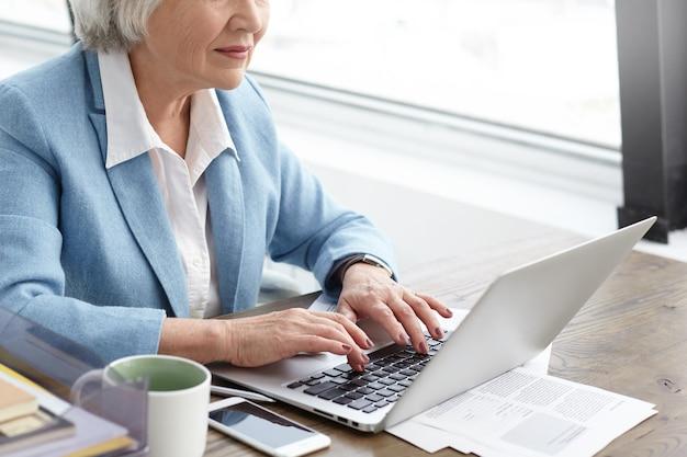 Bijgesneden schot van senior zakenvrouw met grijs haar en gerimpelde handen typen op laptop tijdens het werken op haar kantoor. stijlvolle volwassen blanke vrouw draagt blauw pak met behulp van gadgets voor werk Gratis Foto