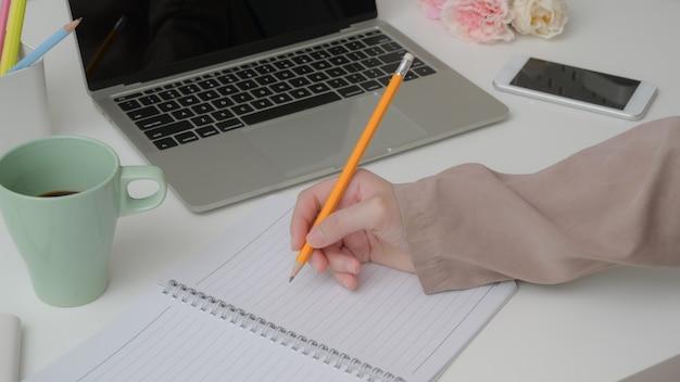 Bijgesneden schot van universiteitsstudent korte notitie over notebook tijdens het lezen van tekst Premium Foto