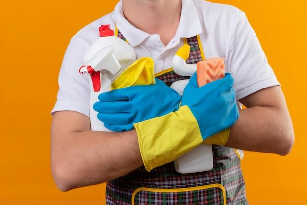 Bijgesneden weergave van man met schort en rubberen handschoenen met schoonmaakbenodigdheden en spons over geïsoleerde oranje achtergrond Gratis Foto