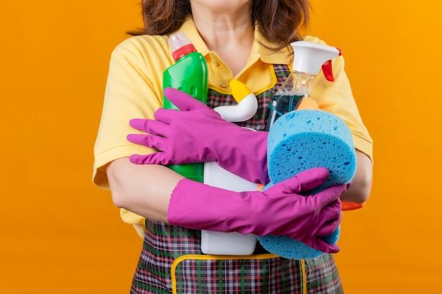 Bijgesneden weergave van vrouw die schort en rubberhandschoenen draagt die schoonmakende hulpmiddelen houden die zich over geïsoleerde oranje achtergrond bevinden Gratis Foto