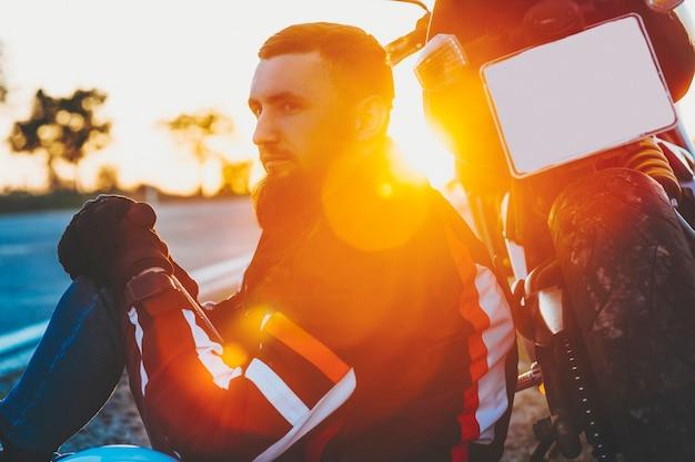 Bijgesneden zijaanzicht van aantrekkelijke bebaarde man in beschermend jasje zit 's avonds op het achterwiel van de motorfiets op onscherpe achtergrondverlichting achtergrond van lege weg Premium Foto
