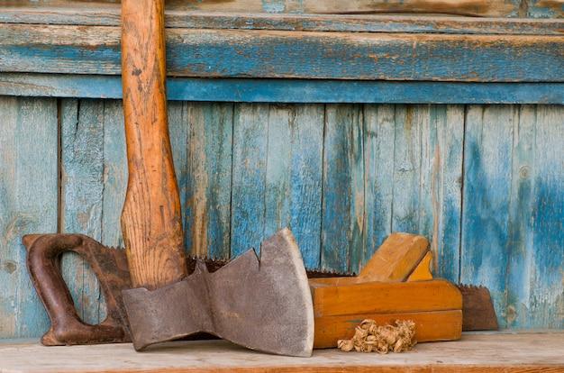 Bijl, schaafmachine en zaag op een oude houten tafel, chips Premium Foto