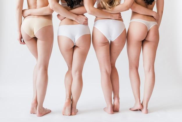 Bijsnijdpoten van vrouwelijke groep in ondergoed die zich in rij bevinden Gratis Foto