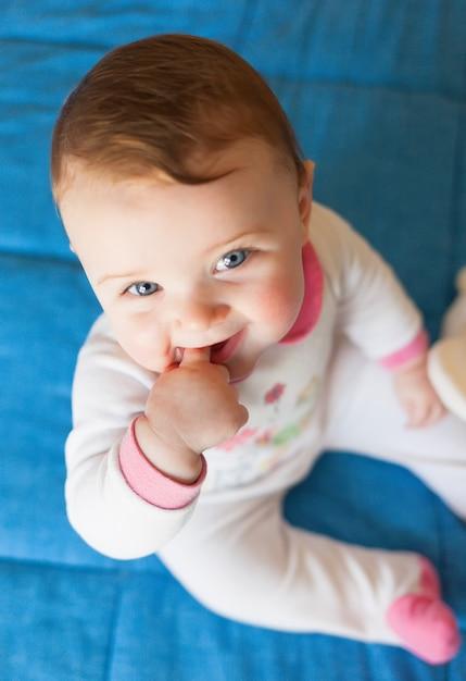 Bijtringen concept. babymeisje met vinger in mond. Premium Foto