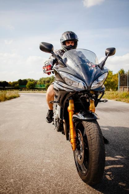 Biker rijden op de zwarte motor Gratis Foto