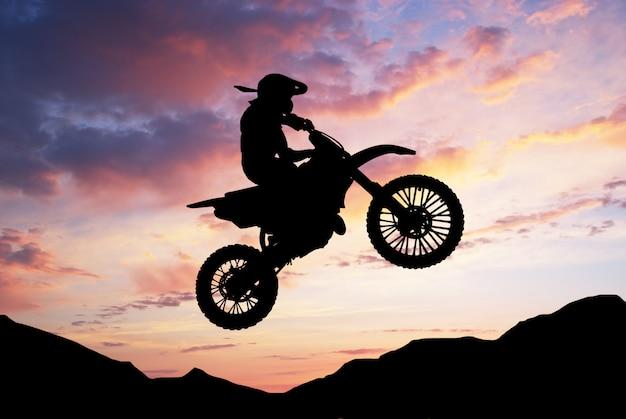 Biker silhouet springen met zijn motorcross motorfiets Premium Foto