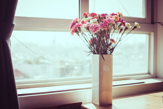 Binnen bloem op de vensterbank. Witte vaas, pot. Gordijnen, tule ...
