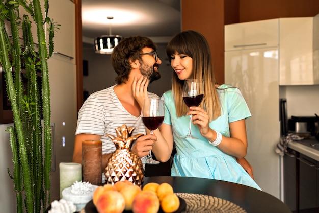 Binnen romantisch familieportret van vrij jong getrouwd stel romantische avond samen doorbrengen, thuis drinken van rode wijn en ontspannen. Gratis Foto