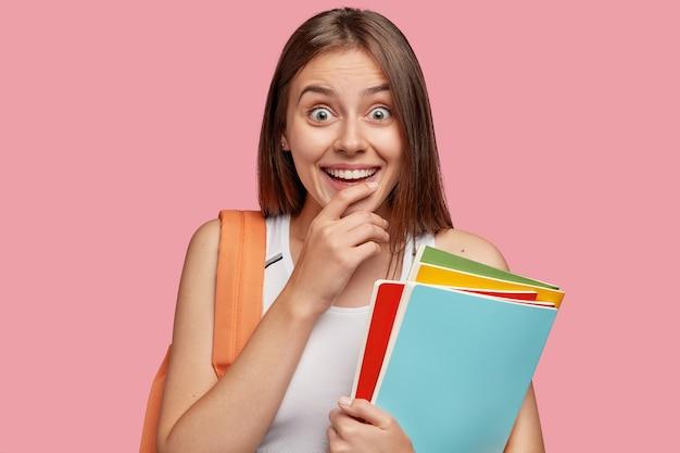 Binnen schot van aangenaam uitziende vrolijke vrouw met brede glimlach, houdt de hand op de kin, kijkt verbaasd, gekleed in een casual outfit, draagt boeken Gratis Foto