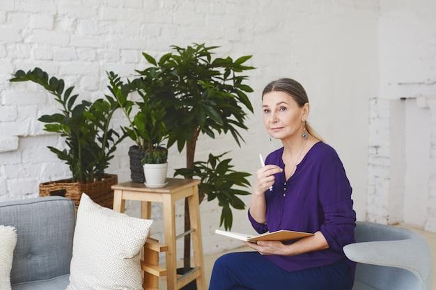 Binnen schot van aantrekkelijke peinzende middelbare leeftijd europese vrouwelijke business coach zittend in lichte ruime kamer, omringd met modern meubilair en plantenpotten, schema in haar dagboek controleren Gratis Foto