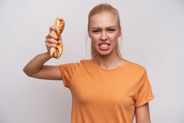 Binnen schot van boze jonge mooie blonde vrouw gekleed in vrijetijdskleding gewelddadig kijken naar camera en hotdog verfrommelen in opgeheven hand, staande tegen een witte achtergrond Gratis Foto