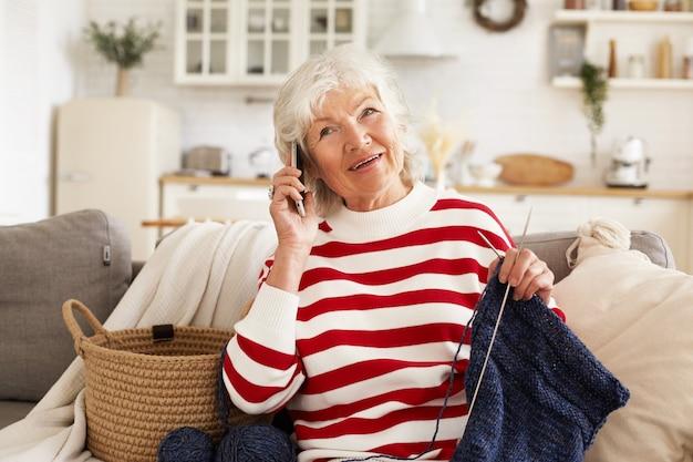 Binnen schot van charmante europese gepensioneerde vrouw met grijze haren genieten van vrije tijd thuis, trui breien voor zoon met behulp van naalden, telefoongesprek. gelukkig oudere vrouw praten op mobiel Gratis Foto