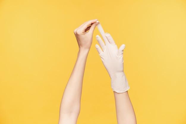 Binnen schot van de hand van de jonge blanke vrouw die witte handschoen uit de andere hand trekt met middelvinger, geïsoleerd over oranje achtergrond. menselijke handen concept Gratis Foto