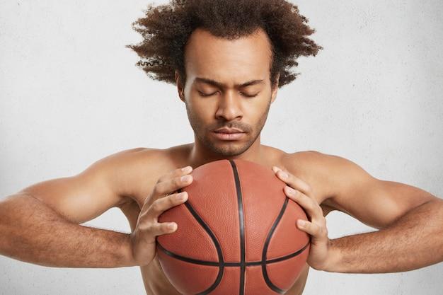 Binnen schot van ernstige geconcentreerde basketbalspeler met bal bereidt zich alleen voor op belangrijke wedstrijd Gratis Foto