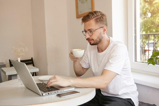 Binnen schot van geconcentreerde jonge mooie man in wit t-shirt, werken op een laptop in café, koffie drinken en bedachtzaam kijken naar scherm Gratis Foto