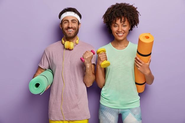 Binnen schot van gelukkig gemotiveerde vrouw en man vrienden hebben dagelijkse trainingen in de sportschool, werken aan biceps, heffen halters Gratis Foto