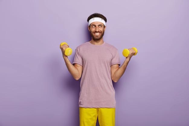 Binnen schot van gelukkig man met borstelharen, heft twee armen met gewichten, gekleed in casual outfit, treinen op biceps Gratis Foto