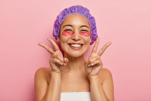 Binnen schot van goed uitziende lachende aziatisch meisje vredesgebaar maken met beide handen, geniet van uderoogbehandeling, collageen patches toepast, bezoek schoonheidsspecialist draagt douchemuts op hoofd. gezichtsverzorging concept Gratis Foto