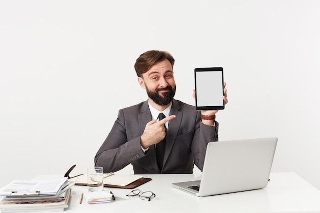 Binnen schot van jonge brunette man in formele kleding zittend aan de werktafel en op zoek naar voorzijde met een ironisch gezicht, tablet pc te houden en erop te wijzen met opgeheven hand Gratis Foto