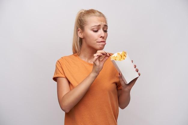 Binnen schot van jonge langharige blonde dame die een papieren doos met frietjes houdt en er opgewonden naar kijkt, het wil eten, maar zich zorgen maakt over extra calorieën, geïsoleerd op witte achtergrond Gratis Foto