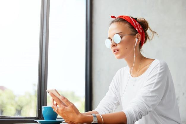 Binnen schot van jonge leuke vrouw draagt rode hoofdband en zonnebril, luistert favoriete compositie van afspeellijst via mobiele telefoon, verbonden met draadloos internet en oortelefoons in gezellige koffiebar Gratis Foto