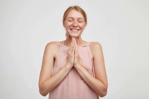 Binnen schot van knappe jonge roodharige dame met casual kapsel glimlachend gelukkig met gesloten ogen en vouwen van verhoogde handpalmen, staande op witte achtergrond Gratis Foto