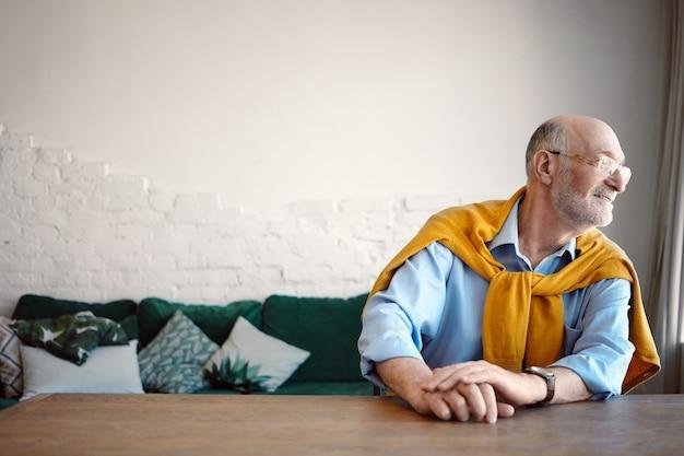 Binnen schot van modieuze grijze haren bebaarde blanke senior mannelijke psycholoog in blauw shirt en brillen zittend aan een bureau thuis kantoor en kijken door raam in afwachting van de klant. Gratis Foto