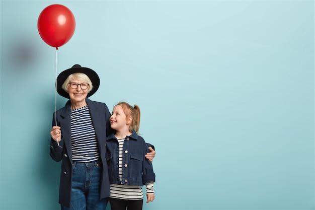 Binnen schot van modieuze senior vrouw omhelst klein kind, geniet van tijd samen doorbrengen Gratis Foto