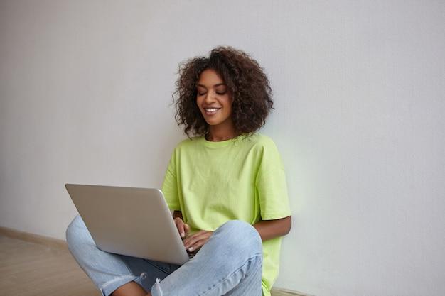 Binnen schot van mooie jonge vrouw met donkere huid zittend op de vloer met laptop, scherm kijken met oprechte glimlach, handen houden op toetsenbord Gratis Foto