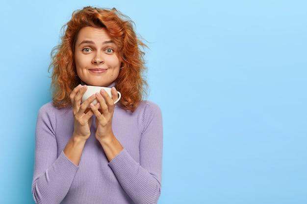 Binnen schot van mooie roodharige meisje heeft koffiepauze, houdt witte mok met aromatische drank, glimlacht en kijkt, geniet van een leuk gesprek terwijl het drinken van thee in de ochtend, nieuws bespreekt Gratis Foto