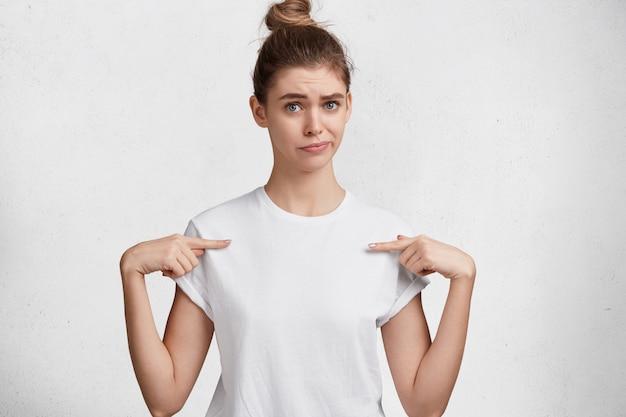 Binnen schot van ongelukkige jonge schattige vrouw met blauwe ogen, haarknoop, gekleed in een casual wit t-shirt, geeft op lege kopie ruimte van t-shirt aan, adverteert kleding, geïsoleerd op studio achtergrond. Gratis Foto