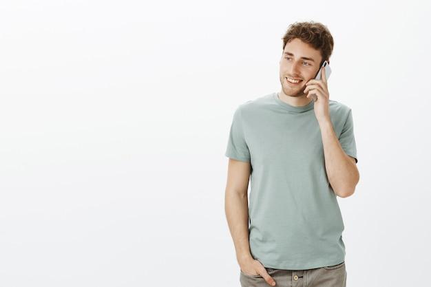 Binnen schot van ontspannen charmante europese man met blond haar, smartphone in de buurt van oor houden en naar links staren met een brede glimlach, terloops praten met zus Gratis Foto