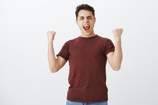 Binnen schot van positieve triomfen knappe voetbalfan in casual rood t-shirt Gratis Foto