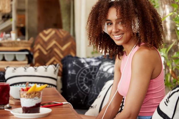 Binnen schot van positieve vrouw met borstelige kapsel, mobiele applicatie gebruikt, geniet van favoriete liedje, zit in gezellig restaurant, eet smakelijk dessert. afro-amerikaanse vrouw luistert naar muziek in de koptelefoon Gratis Foto