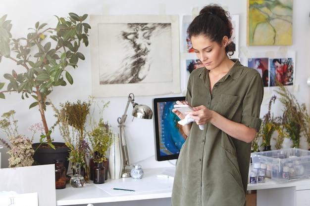 Binnen schot van prachtige mooie brunette jonge vrouw ontwerper tekstbericht typen op mobiele telefoon, online winkelen, verf, canvas of frame bestellen. mensen, kunst, creativiteit en technologie concept Gratis Foto