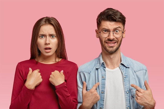 Binnen schot van verontwaardigde blanke jonge vrouw en man wijzen op zichzelf Gratis Foto