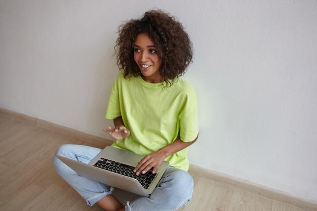 Binnen schot van vrij donkerharige gekrulde vrouw zittend op de vloer met laptop en op zoek naar persoon achter de schermen, glimlachend en gebaren met de hand Gratis Foto