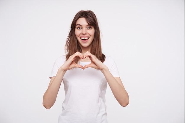 Binnen schot van vrolijke jonge mooie donkerharige vrouw die hart met opgeheven handen vouwt en vreugdevol kijkt met een brede oprechte glimlach, geïsoleerd over witte muur Gratis Foto