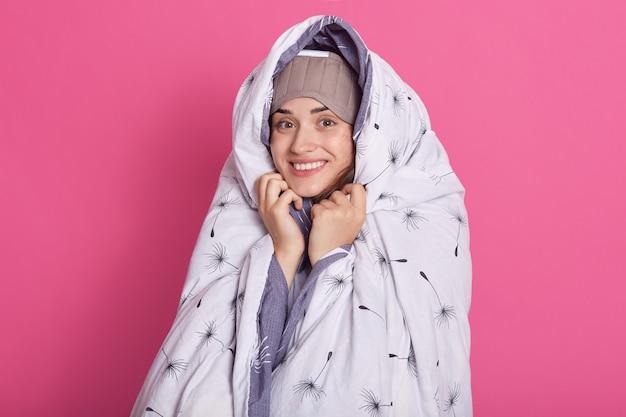 Binnen studioschot van het glimlachen van leuke aantrekkelijke vrouwelijke status geïsoleerd over roze Gratis Foto