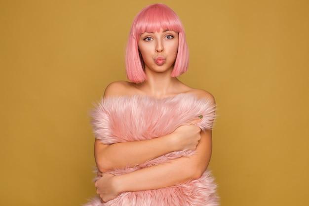 Binnenfoto van een mooie jonge blauwogige rozeharige dame die haar lippen pruilt terwijl ze opgewonden kijkt, een pluizig kussen in haar handen houdt terwijl ze over de mosterdmuur staat Gratis Foto