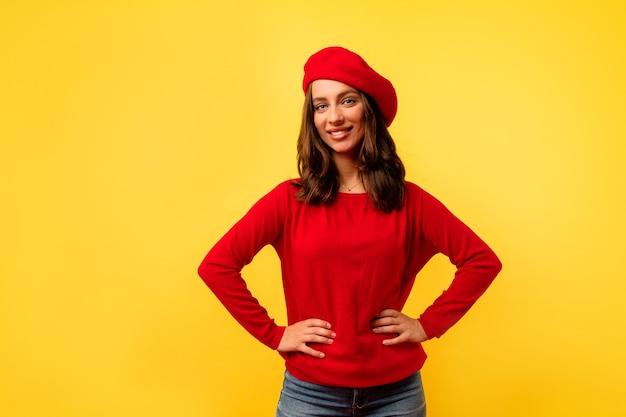 Binnenfoto van jonge europese charmante dame met kort kapsel in rode stijlvolle trui en baret poseren over gele muur Gratis Foto