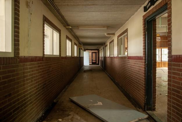 Binnenlands schot van een lege zaal van een verlaten school met gebroken deuren Gratis Foto