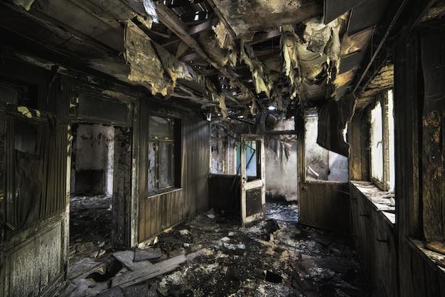 Binnenopname van een verlaten verwoest gebouw met verbrande muren en versleten deuren Gratis Foto